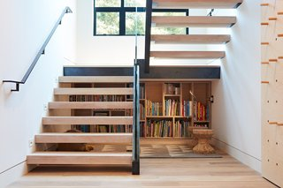 "In a family home in Mill Valley, California, Lauren Goldman of l'oro designs kept her clients' goals of ""modern yet accessible"" in mind while also looking for opportunities to add functionality. This proved successful when she discovered that the empty space under the steel-and-glass stair landing was the perfect scale for children to sit and read under. The team was inspired to create a kid-sized library, turning a useless space into a perfectly cozy reading nook."