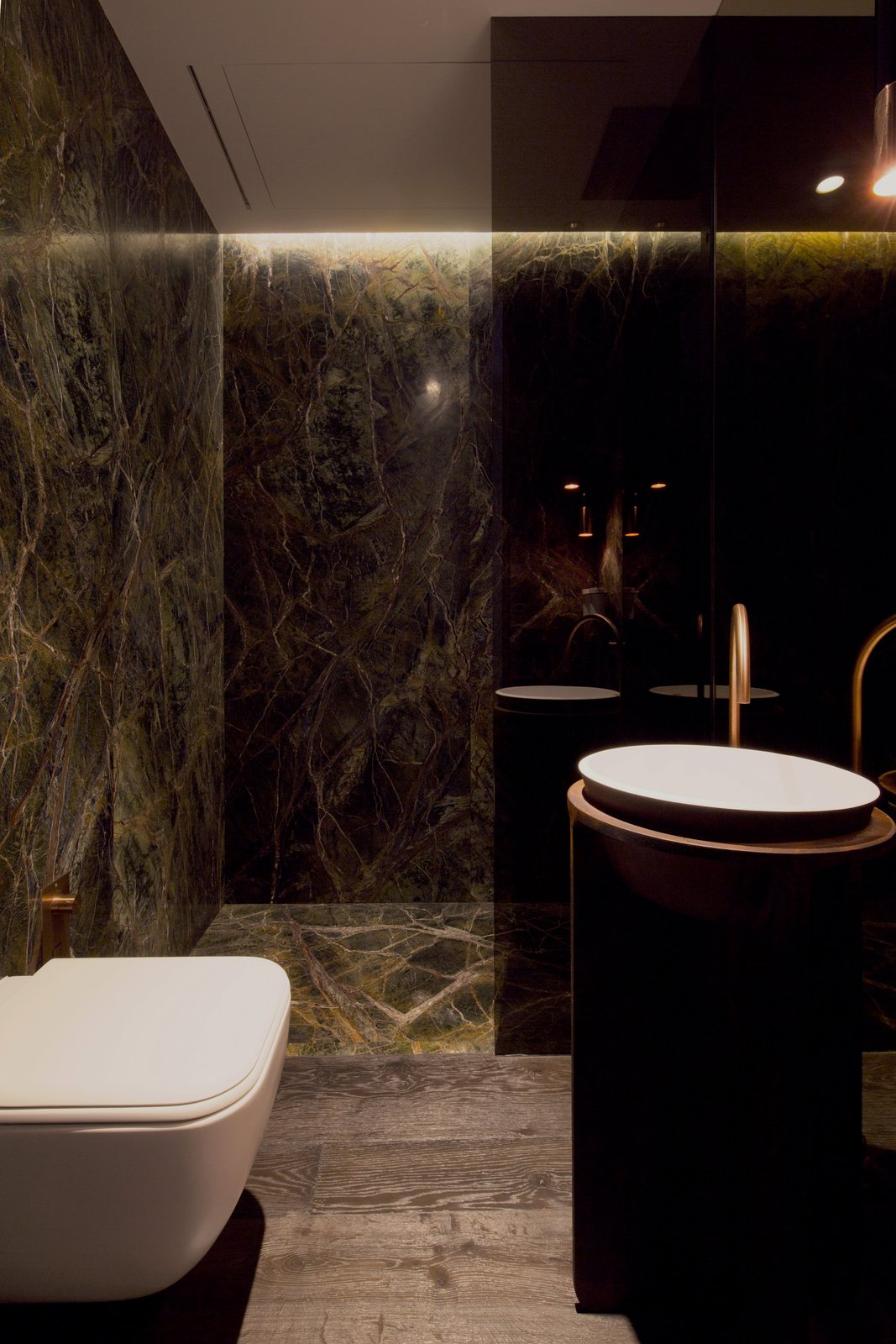 Bath Room, Dark Hardwood Floor, Vessel Sink, Ceiling Lighting, Marble Wall, Open Shower, and One Piece Toilet  Photo 12 of 13 in A Family's Kiev Apartment Is Filled With Copper, Marble, and a Sophisticated Palette