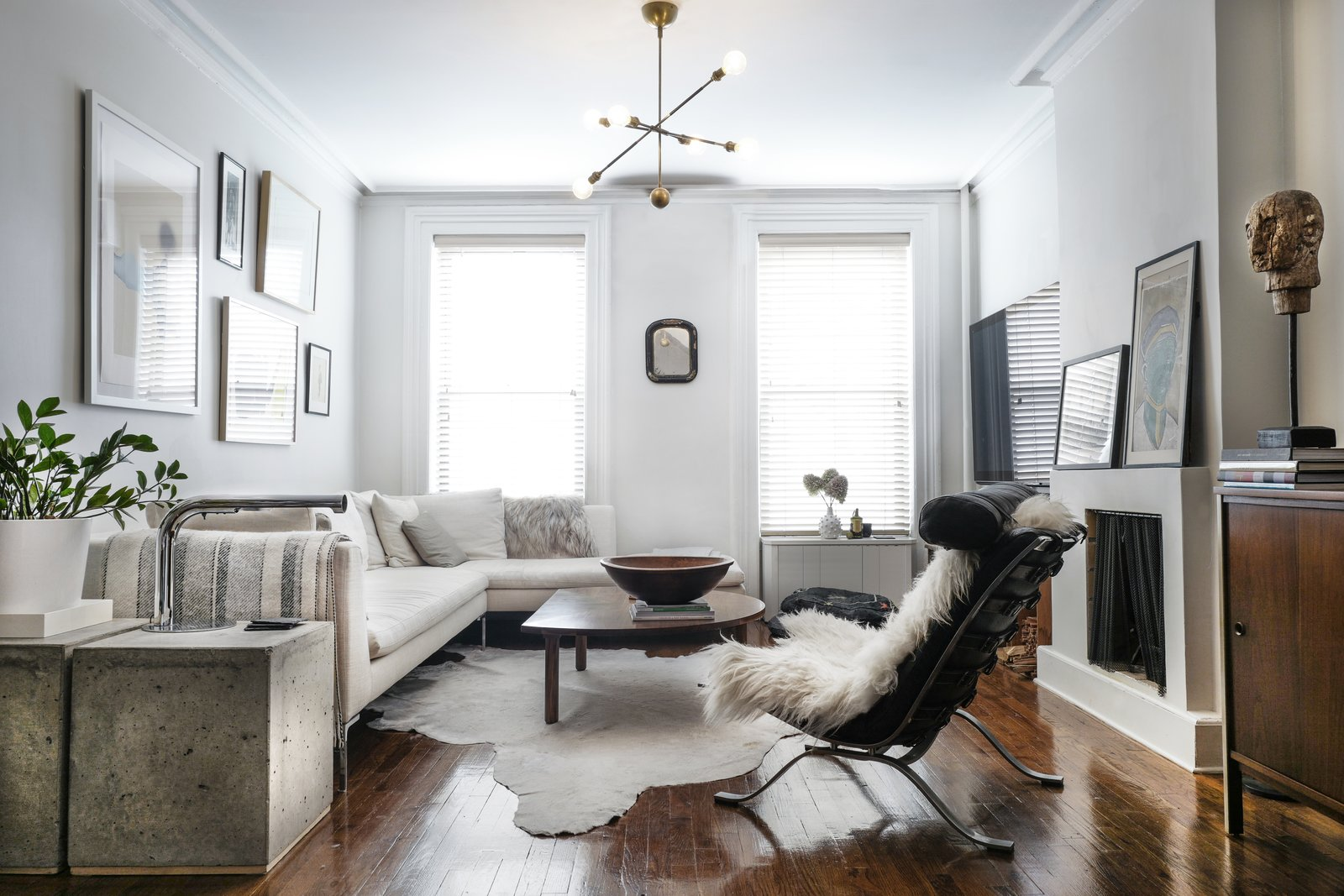 Living Room, Sectional, Media Cabinet, Dark Hardwood Floor, Chair, Standard Layout Fireplace, Wood Burning Fireplace, End Tables, Coffee Tables, Storage, and Pendant Lighting  Photo 4 of 16 in A Design Duo's 19th-Century Brooklyn Townhouse Is Filled With Art They Love