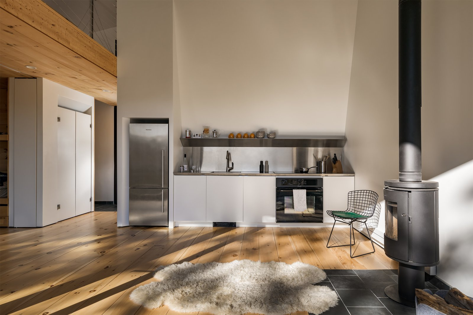 Kitchen, Medium Hardwood Floor, White Cabinet, Refrigerator, and Metal Counter  Photo 15 of 18 in A Prefab Cabin in New Hampshire Is a Magnificent Mountain Retreat