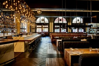 Guests are greeted by plush leather booths and classic hardwood floors in the chic bar area.