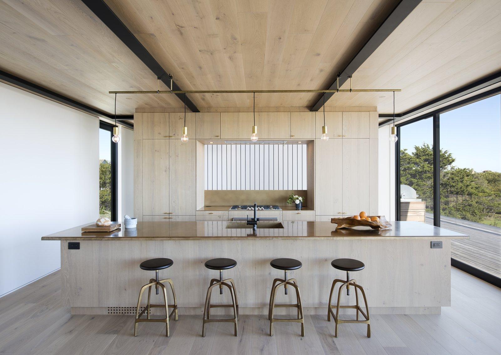 Kitchen, Ceiling Lighting, Light Hardwood Floor, Wood Cabinet, Recessed Lighting, Engineered Quartz Counter, Range, Drop In Sink, and Refrigerator  Best Photos from Amagansett Landmark
