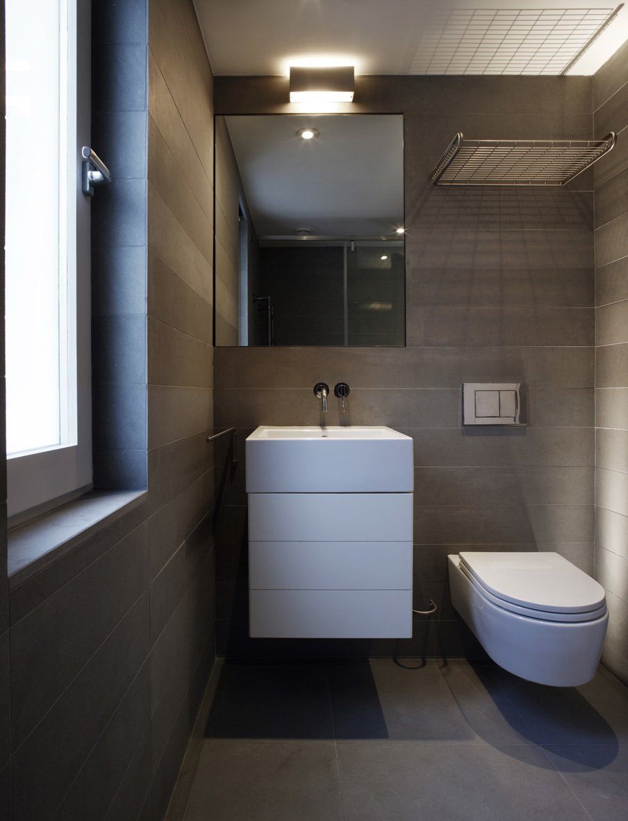 Bath Room, Concrete Floor, Vessel Sink, Ceiling Lighting, Stone Tile Wall, and One Piece Toilet  Elm Grove by Thompson + Baroni