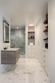 A functional and contemporary master bath becomes a spacious oasis with Afyon Grey marble in the shower, his-and-hers back-to-back vanities, and plenty of custom shelving and storage.