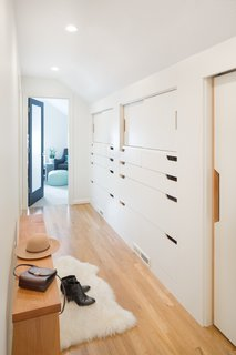 Custom millwork and cabinetry can be a great way to add storage while keeping the hallway looking clean, neat, and bright. Cut-outs in the doors instead of knobs or cabinet handles ensure that hardware doesn't take up any extra space in the narrow corridor.