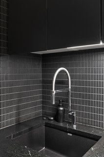 A minimalist black-and-white aesthetic is kept in this apartment kitchen, where elongated black tile is contrasted with lighter gray grout. The countertops are dark soapstone and the cabinets are a dark green-black.