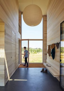 Floor-to-ceiling glazing fills the entryway with light.