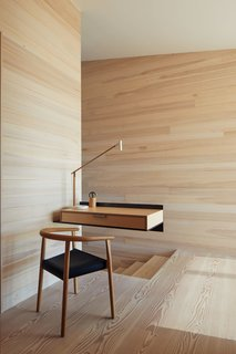 """A cantilevered birch and plywood desk appears to effortlessly float in midair. The wood box is attached to the wall with a blackened structural steel angle. """"It's a place to make a phone call, put down keys, plug in the iPhones,"""" says Ryall. """"We liked the contrast of the structural steel and the more refined wood box, kind of the like the house, which itself is full of contrasts—rough/smooth, dark/light, open/closed."""""""