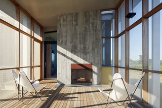 """""""The fireplace extends the season,"""" says Ryall. """"The owners probably use that porch six months out of the year."""" The design team formed the fireplace's concrete facade using rough wood boards to give it a rugged texture."""