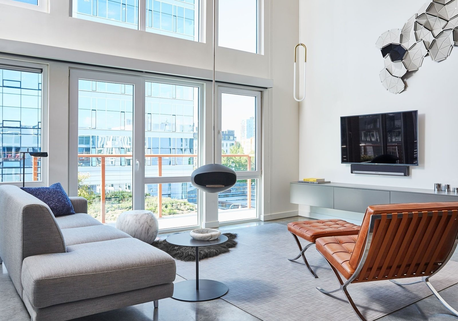 Living Room, Hanging Fireplace, Sofa, Chair, and Concrete Floor  South Lake Union Loft by J+STUDIO