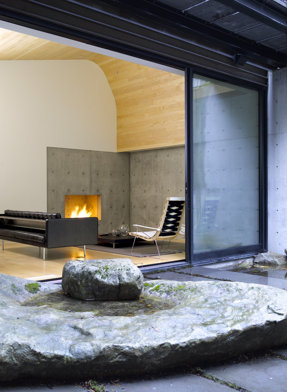Tagged: Living Room, Corner Fireplace, Chair, Light Hardwood Floor, and Sofa.  Courtyard House on a Steep Site by Robert Hutchison Architecture