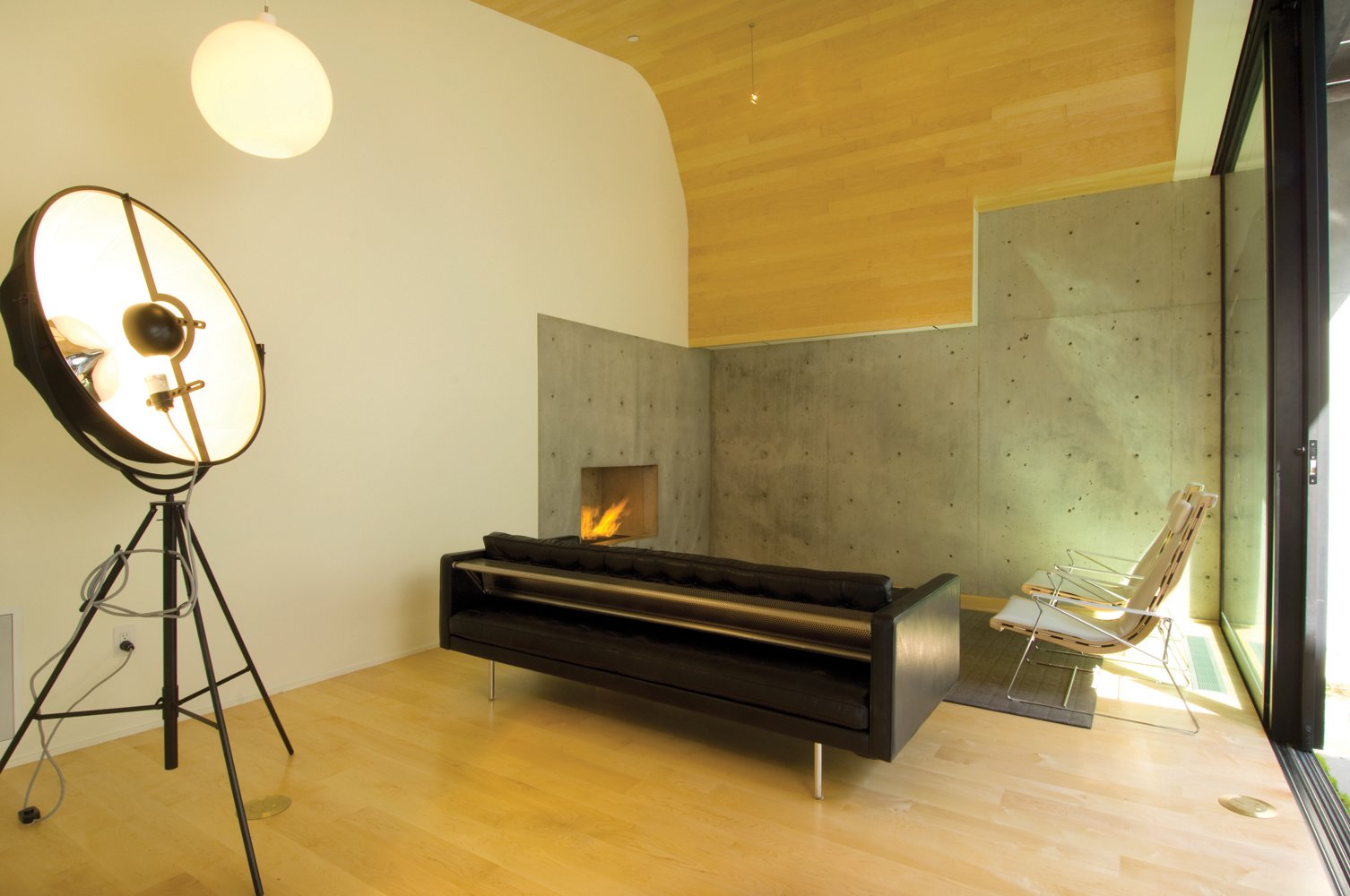 Living Room, Sofa, Chair, Light Hardwood Floor, Ceiling Lighting, and Corner Fireplace  Courtyard House on a Steep Site by Robert Hutchison Architecture