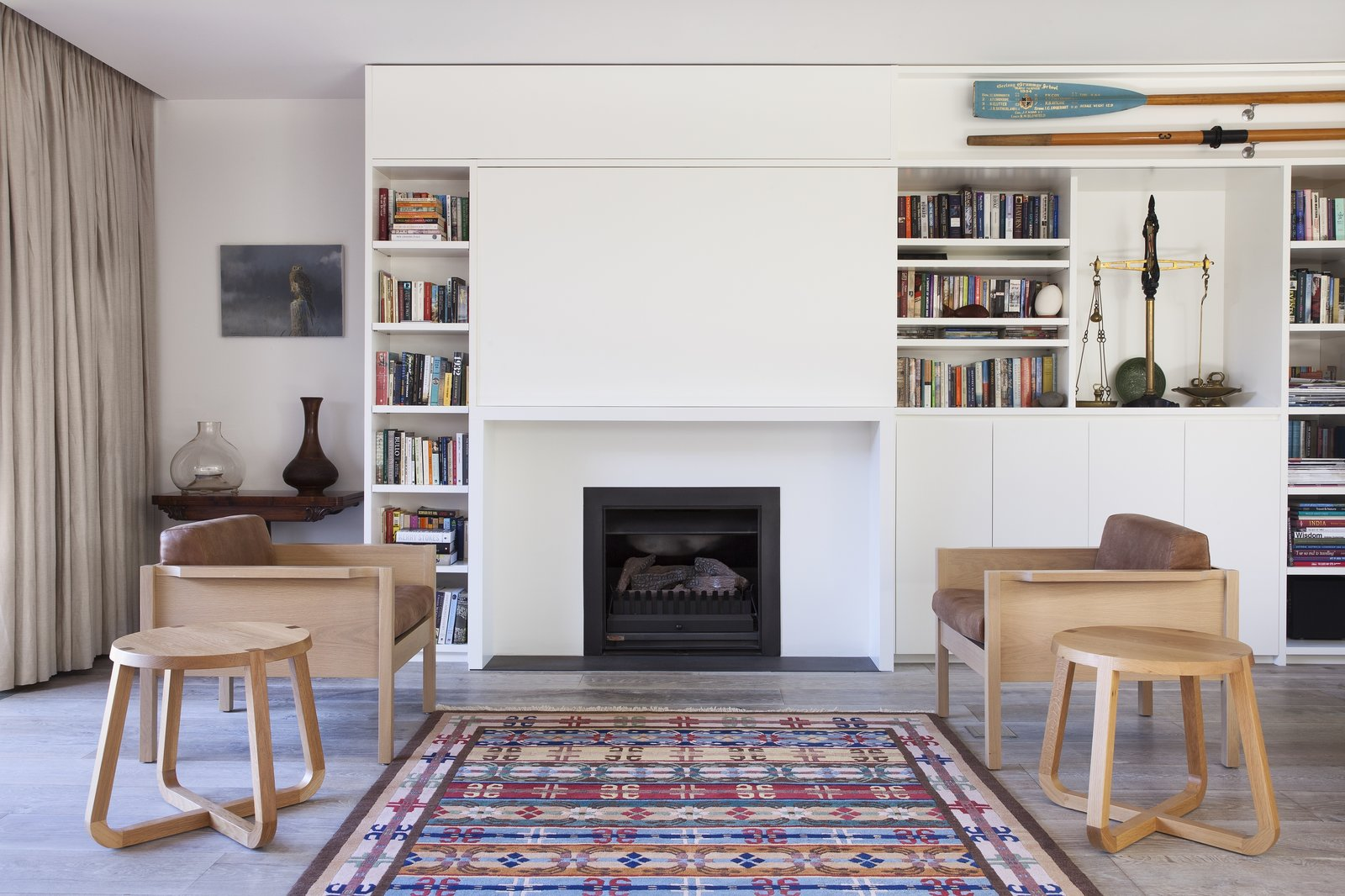 Living Room, Standard Layout Fireplace, Chair, End Tables, Bookcase, and Light Hardwood Floor  Photo 5 of 6 in A Timber-Clad Home in Australia Is a Striking Place to Grow Old In