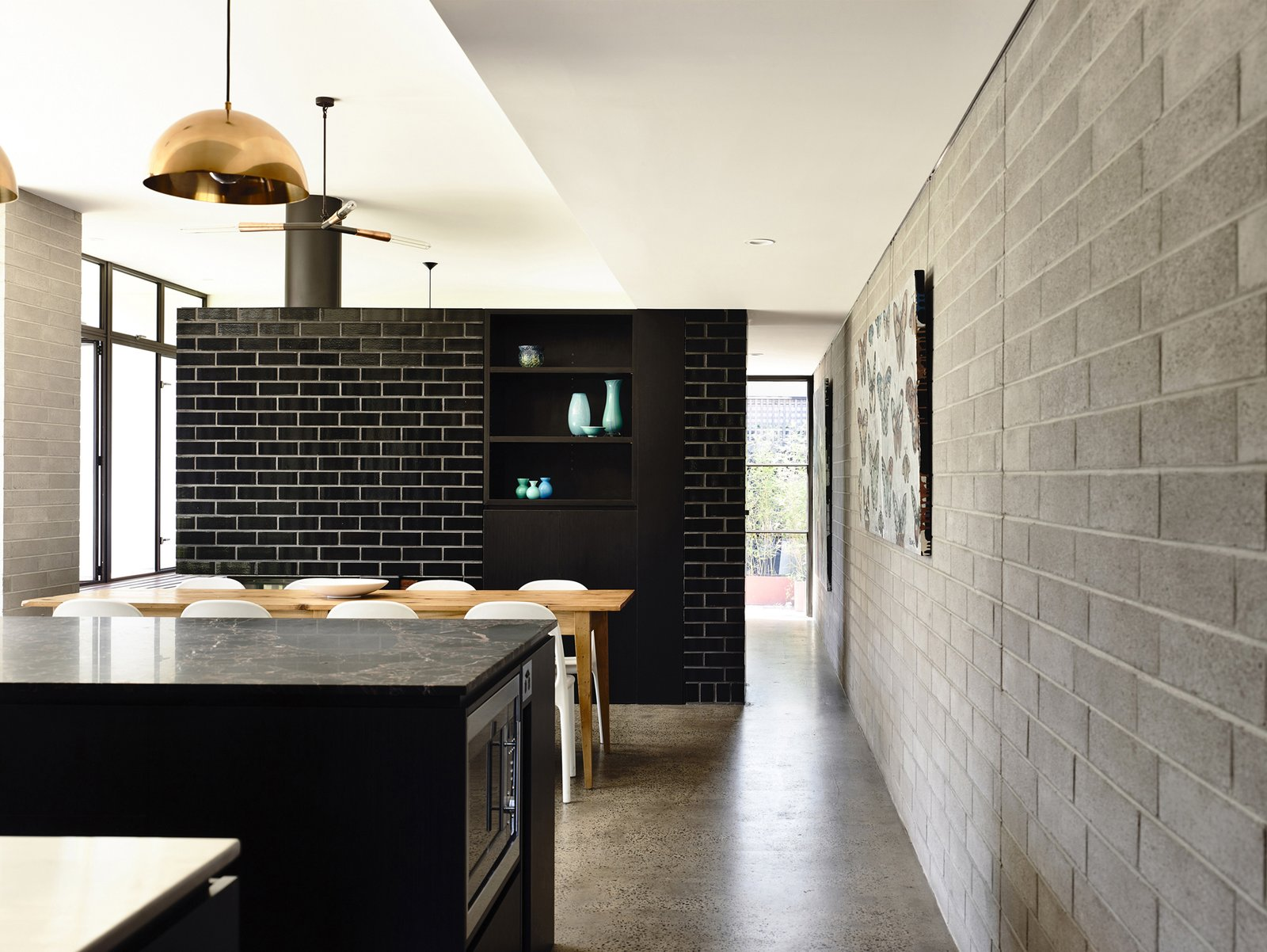 Dining Room, Chair, Table, Pendant Lighting, Concrete Floor, and Wood Burning Fireplace  Photo 6 of 10 in Old Meets New in This Modern Extension to an Edwardian House in Melbourne