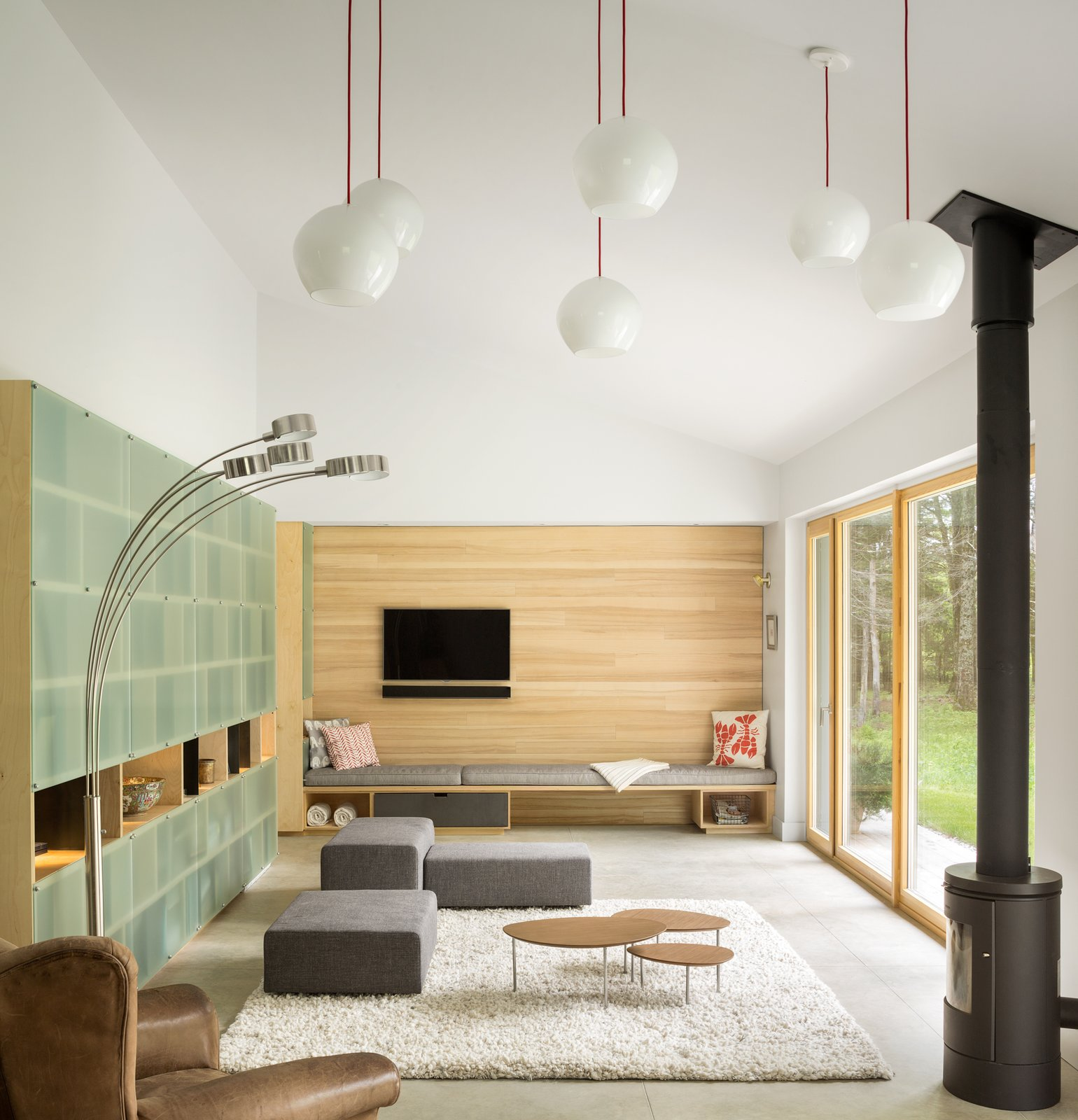 Living Room, Pendant Lighting, Bench, Recliner, Chair, Concrete Floor, Rug Floor, Shelves, Lamps, and Floor Lighting  Best Photos from GO Home Takes the Passive House Approach to Prefab