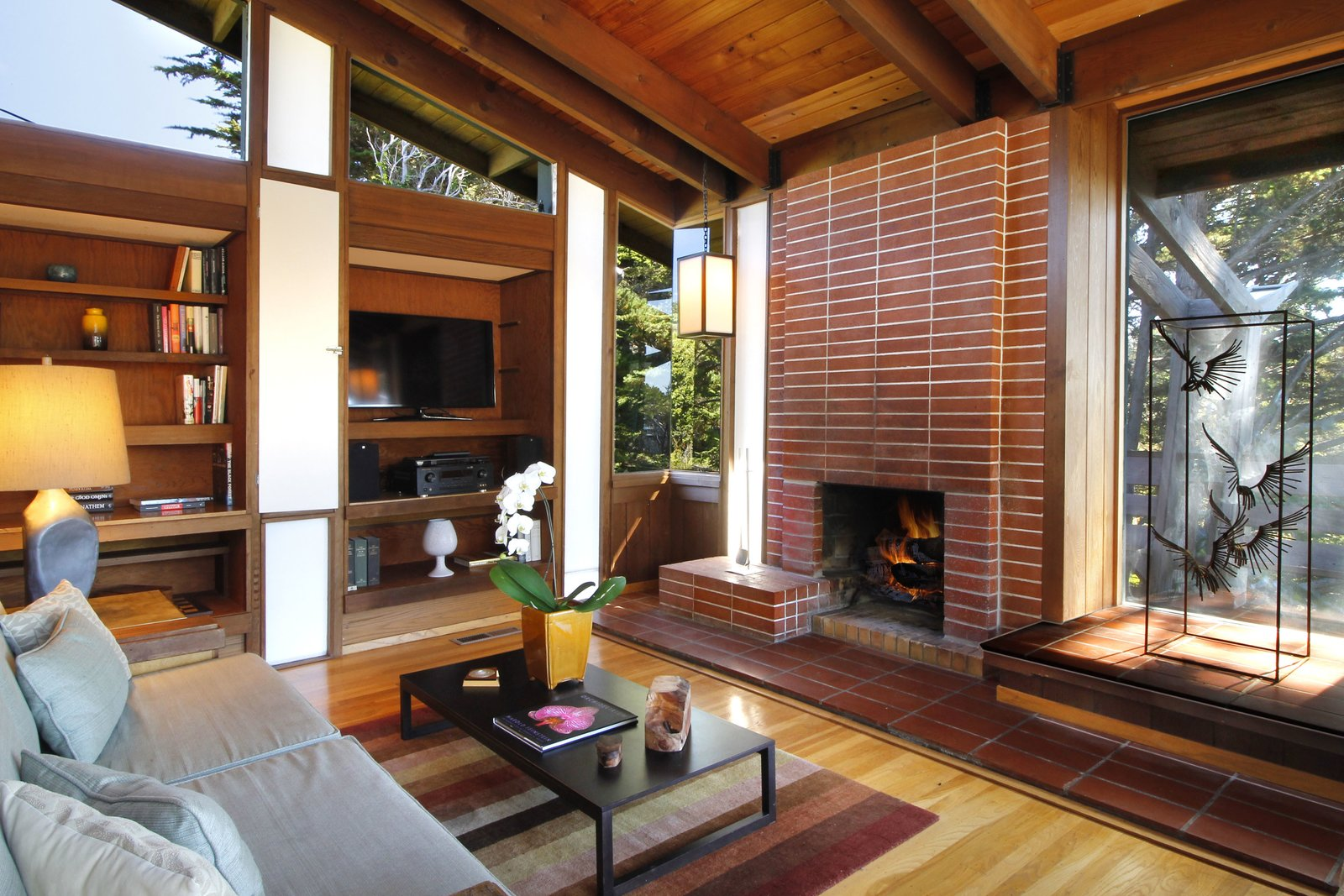 Living Room, Standard Layout Fireplace, Wood Burning Fireplace, Table Lighting, Pendant Lighting, Medium Hardwood Floor, Rug Floor, Coffee Tables, Sofa, and Shelves  Photo 10 of 11 in A Perfectly Preserved Midcentury Pad in Northern California Asks $1.975M