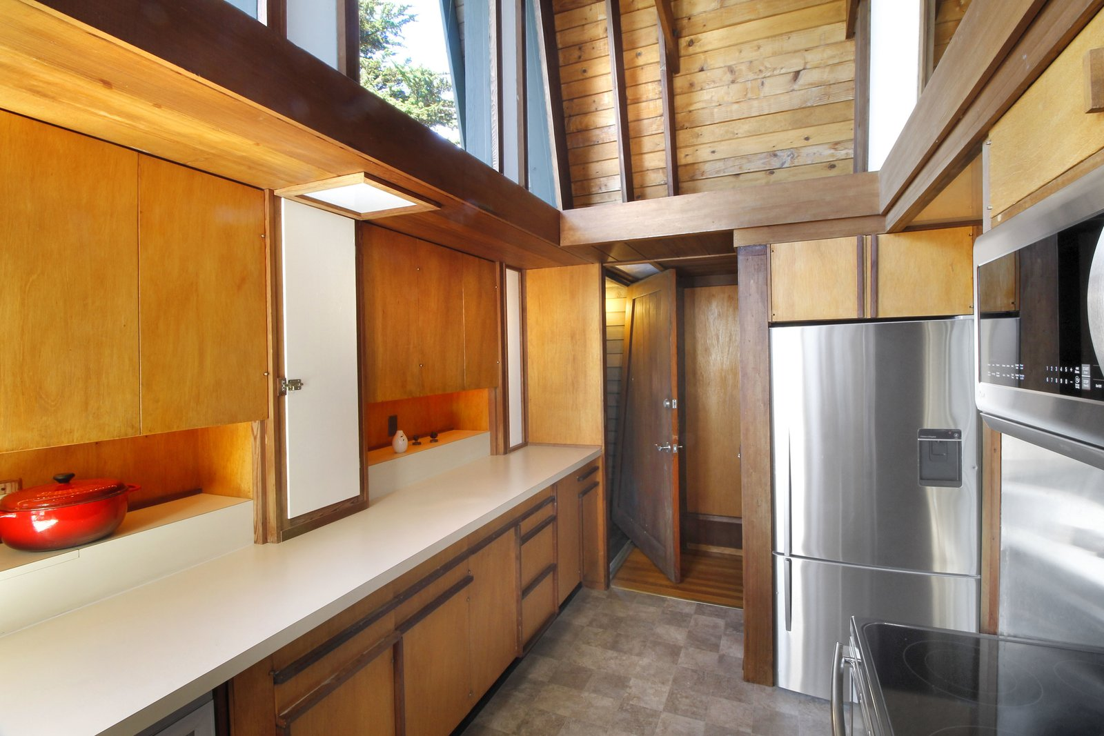 Kitchen, Wood Cabinet, Refrigerator, Microwave, Cooktops, and Wood Backsplashe  Photo 8 of 11 in A Perfectly Preserved Midcentury Pad in Northern California Asks $1.975M