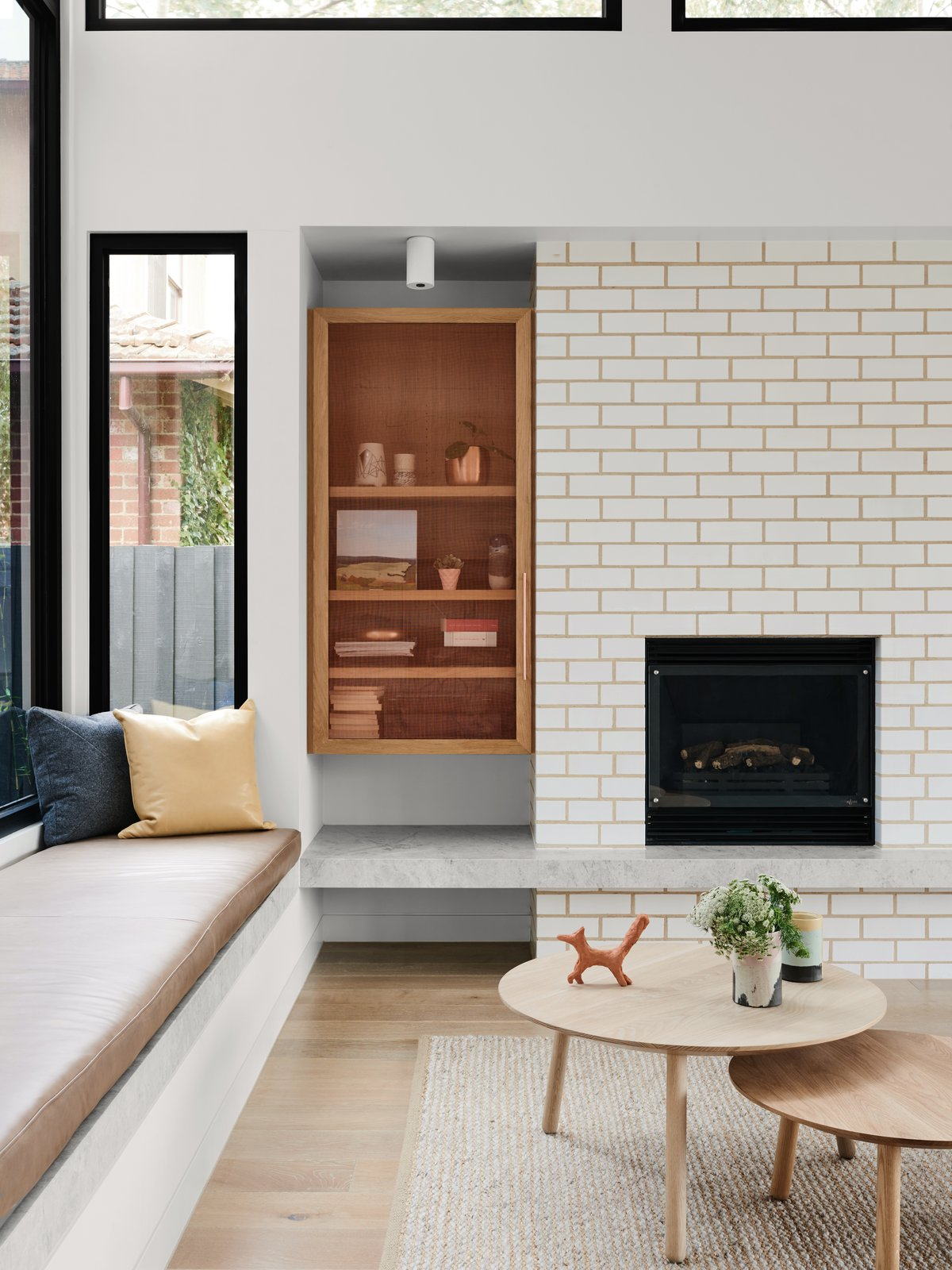 Living Room, Bench, Coffee Tables, Shelves, Standard Layout Fireplace, Rug Floor, Light Hardwood Floor, and Ceiling Lighting  Photo 3 of 10 in A Run-Down Melbourne Bungalow's Makeover Embraces Light and Family Life