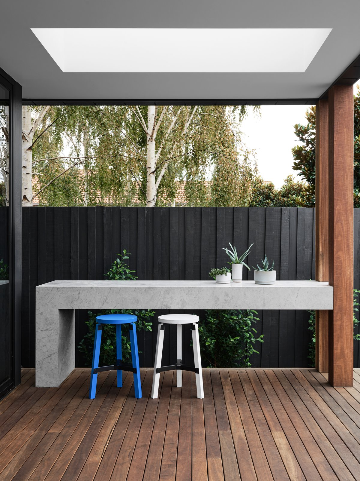 Outdoor, Back Yard, Trees, Decking Patio, Porch, Deck, Wood Patio, Porch, Deck, Vertical Fences, Wall, and Wood Fences, Wall  Photo 4 of 10 in A Run-Down Melbourne Bungalow's Makeover Embraces Light and Family Life