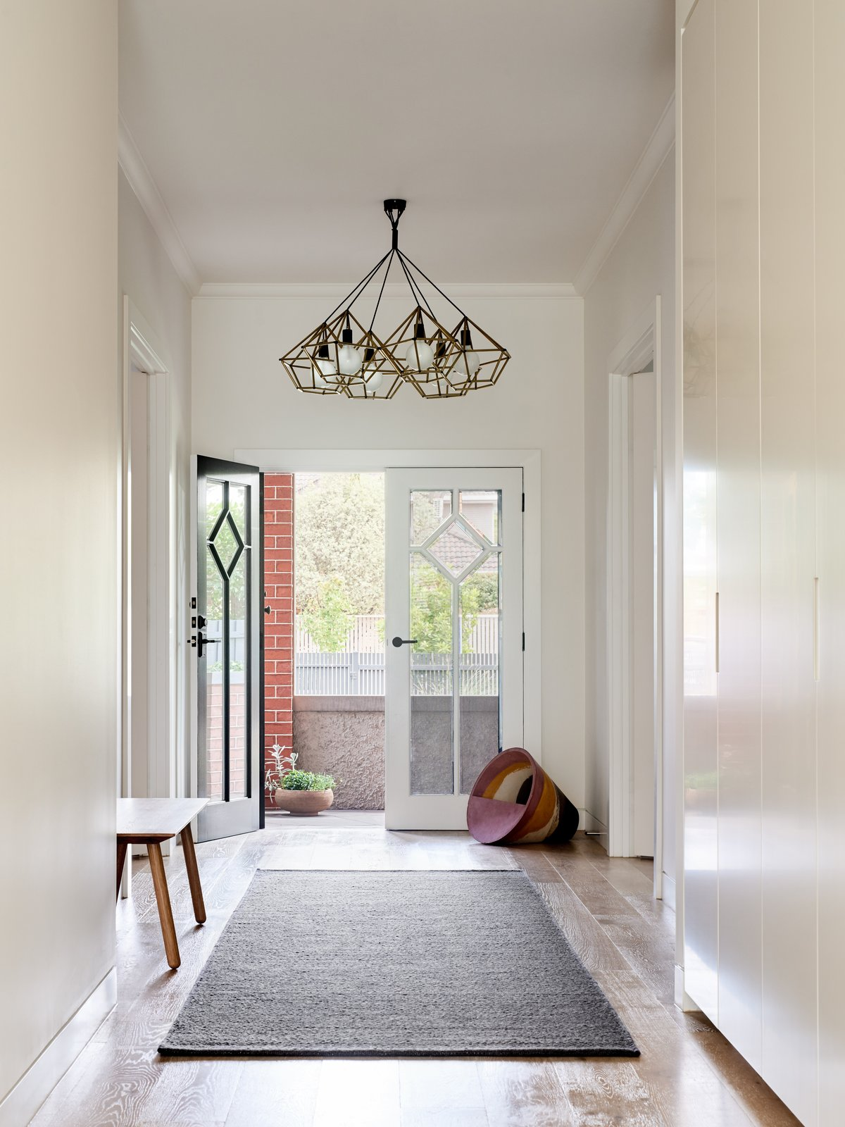 Hallway, Rug Floor, and Medium Hardwood Floor  Photo 5 of 10 in A Run-Down Melbourne Bungalow's Makeover Embraces Light and Family Life