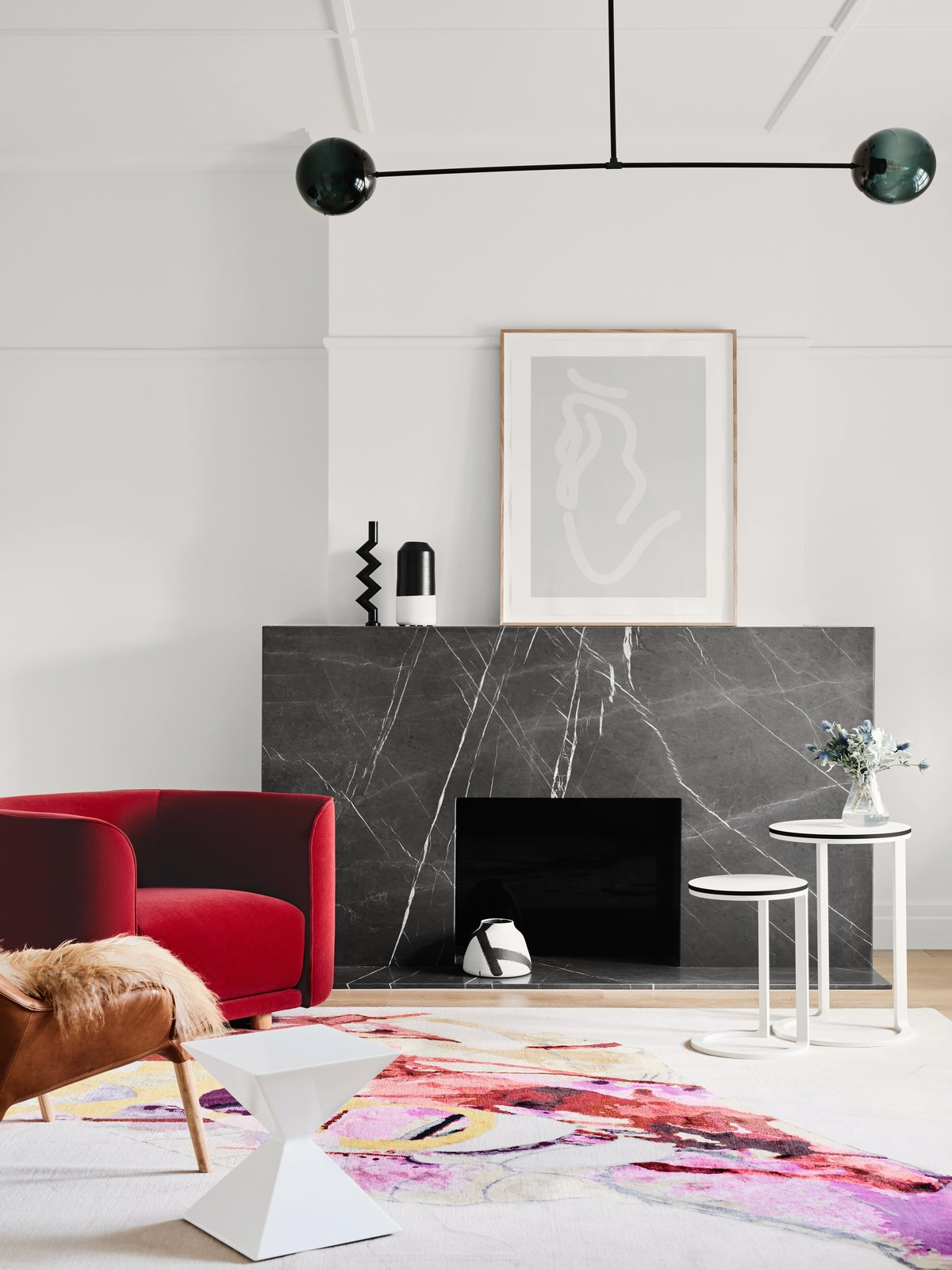 Living Room, Stools, Chair, End Tables, Pendant Lighting, Standard Layout Fireplace, Light Hardwood Floor, and Rug Floor  Photo 6 of 10 in A Run-Down Melbourne Bungalow's Makeover Embraces Light and Family Life