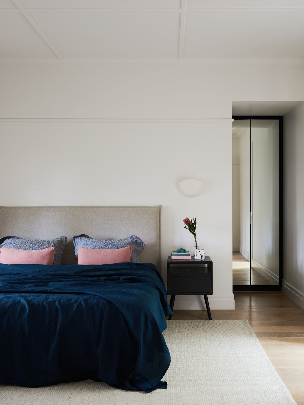 Bedroom, Bed, Night Stands, Wall Lighting, Light Hardwood Floor, and Rug Floor  Photo 9 of 10 in A Run-Down Melbourne Bungalow's Makeover Embraces Light and Family Life
