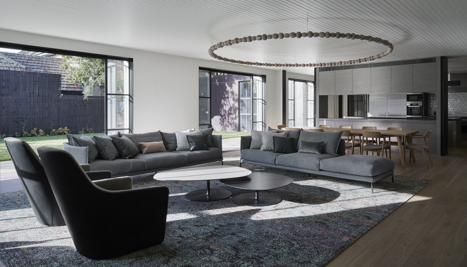 Living Room, Sofa, Coffee Tables, Chair, Medium Hardwood Floor, Rug Floor, and Ceiling Lighting  Photo 8 of 11 in See How Sliding-Glass Pavilions Transformed a Renovated Melbourne Home