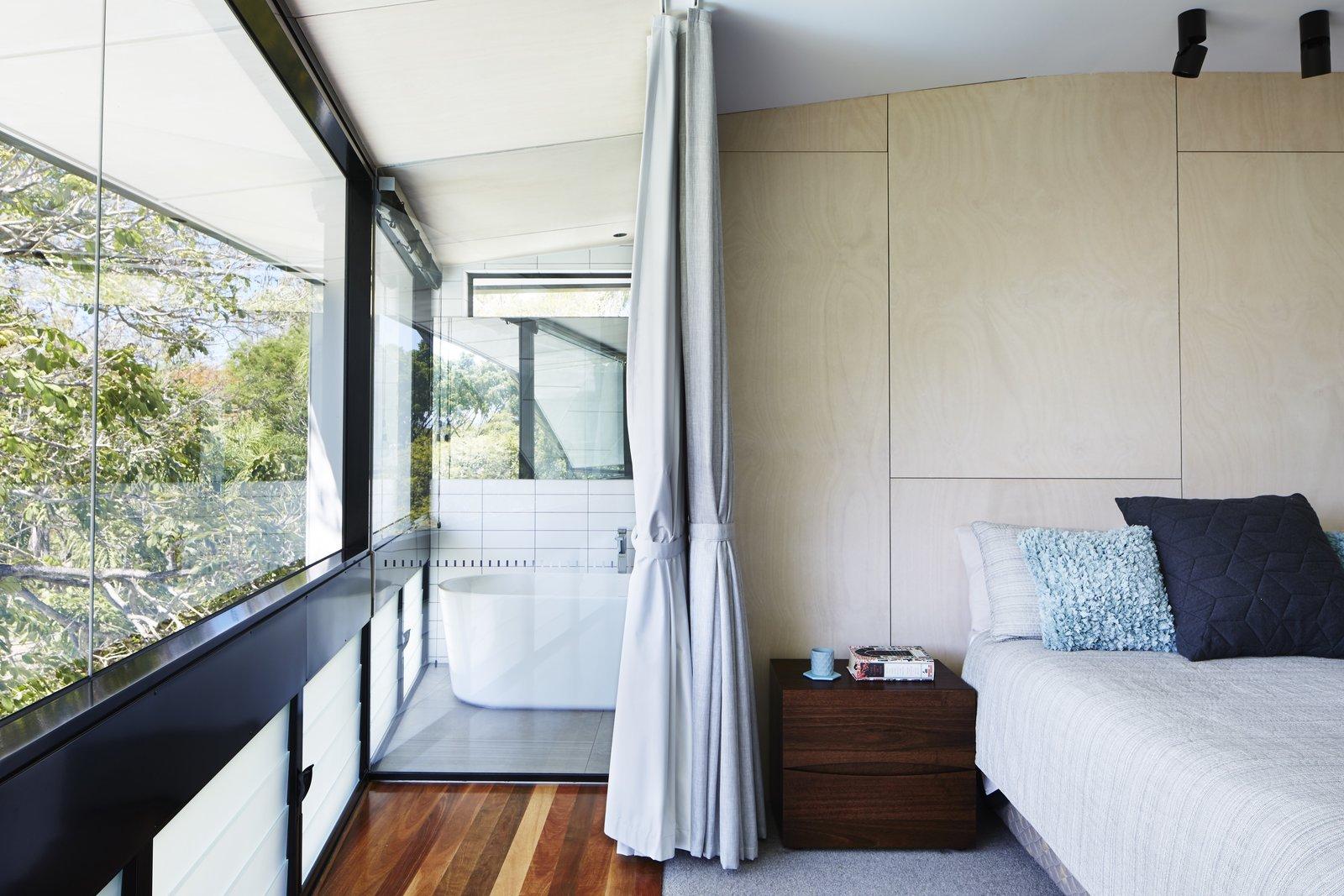 Bedroom, Medium Hardwood Floor, Night Stands, Bed, Ceiling Lighting, and Rug Floor  Photo 5 of 12 in An Edgy Slatted Facade Conceals a Striking Indoor/Outdoor Home in Brisbane