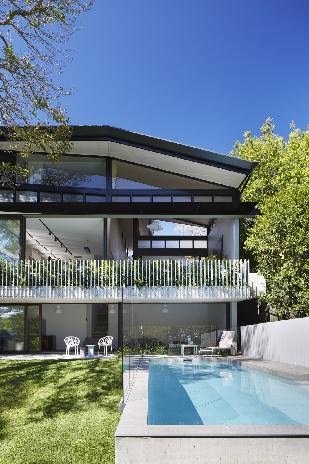 Outdoor, Back Yard, Trees, Grass, Large Pools, Tubs, Shower, Large Patio, Porch, Deck, and Vertical Fences, Wall  Photo 11 of 12 in An Edgy Slatted Facade Conceals a Striking Indoor/Outdoor Home in Brisbane