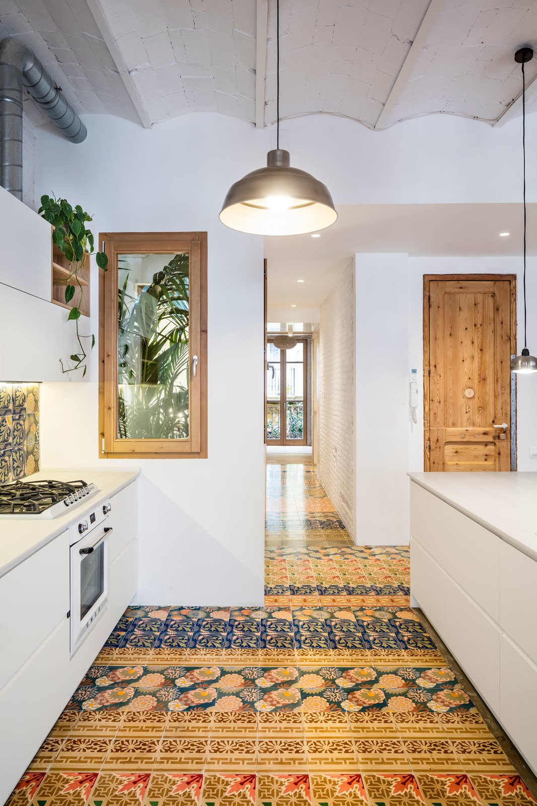 Kitchen, White Cabinet, Ceramic Tile Floor, Ceramic Tile Backsplashe, Pendant Lighting, Cooktops, and Wall Oven  Photo 8 of 14 in A Dramatic Apartment Renovation in Barcelona Features Salvaged Tile and Brick