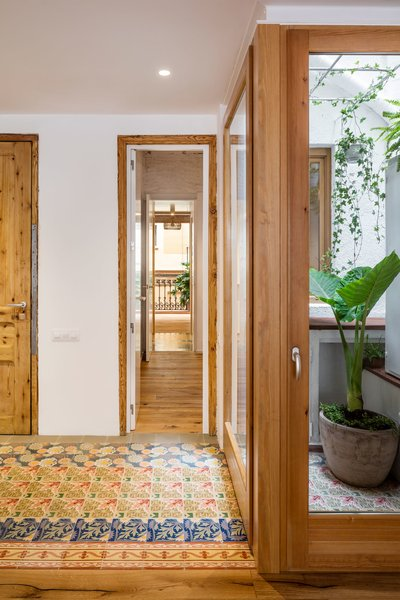 Hallway, Medium Hardwood Floor, and Ceramic Tile Floor  Photo 10 of 14 in A Dramatic Apartment Renovation in Barcelona Features Salvaged Tile and Brick