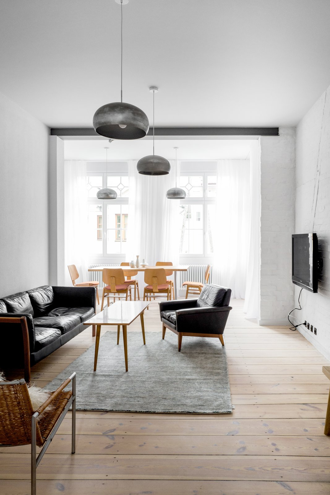 Living Room, Sofa, Chair, Coffee Tables, Pendant Lighting, and Light Hardwood Floor  Best Photos from A Holiday Apartment in Poland With the Perfect Mix of Vintage and Custom Furniture