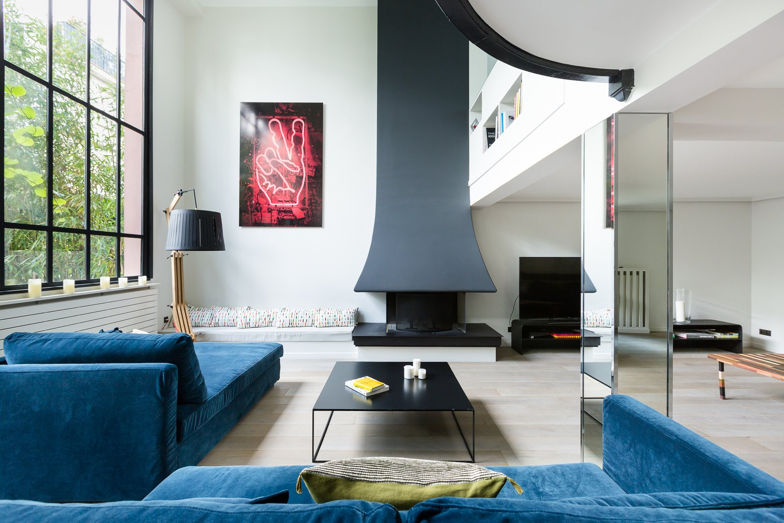 Living Room, Light Hardwood Floor, Bench, Standard Layout Fireplace, Floor Lighting, Sofa, Recliner, Coffee Tables, and Media Cabinet  Photo 3 of 11 in Channel Parisian Glamour With a Stay in This Striking Montmartre Townhouse