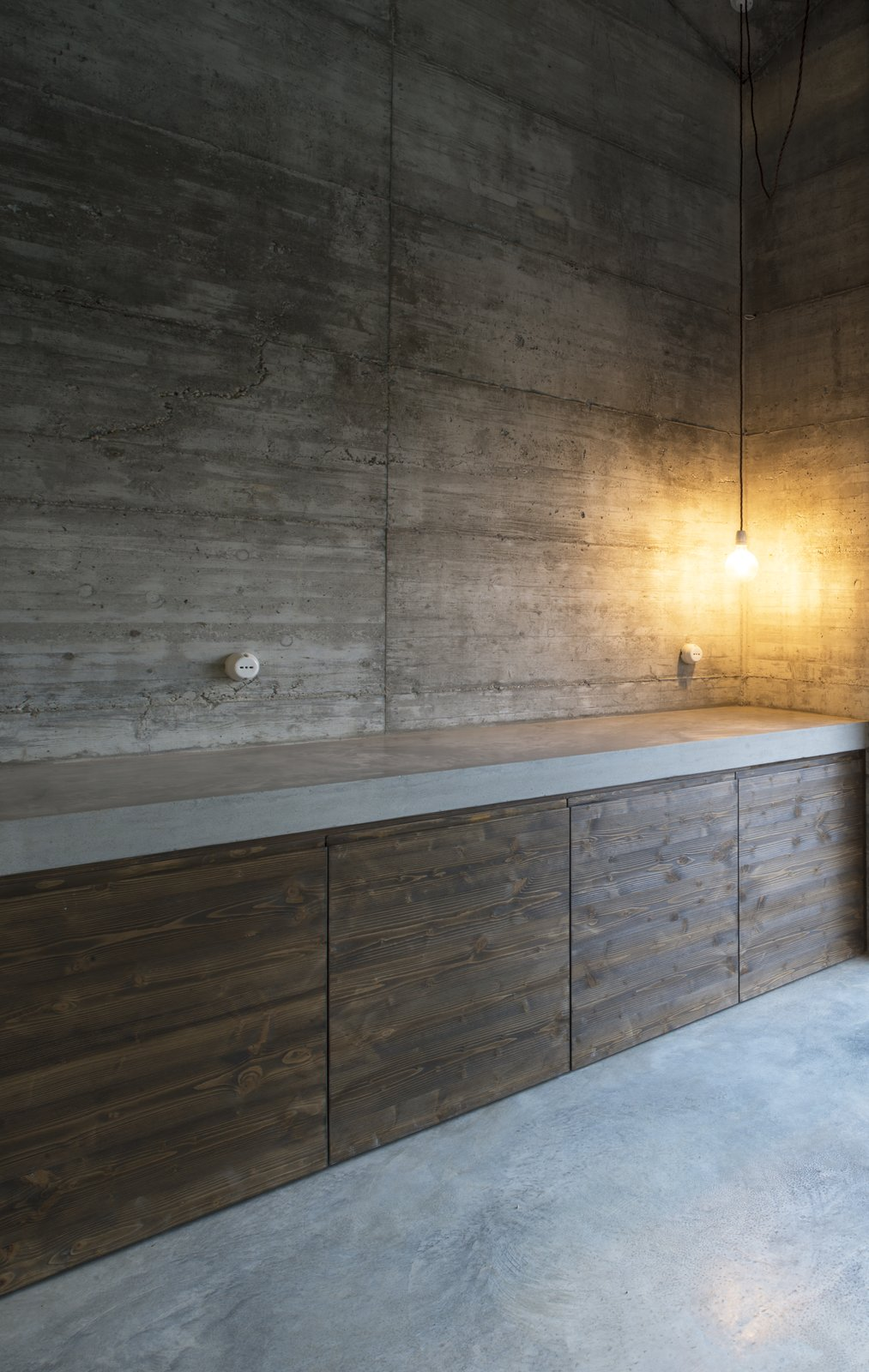 Kitchen, Wood Cabinet, Concrete Counter, Concrete Floor, Pendant Lighting, and Concrete Backsplashe  Best Photos from A Concrete Hideaway in the Italian Countryside