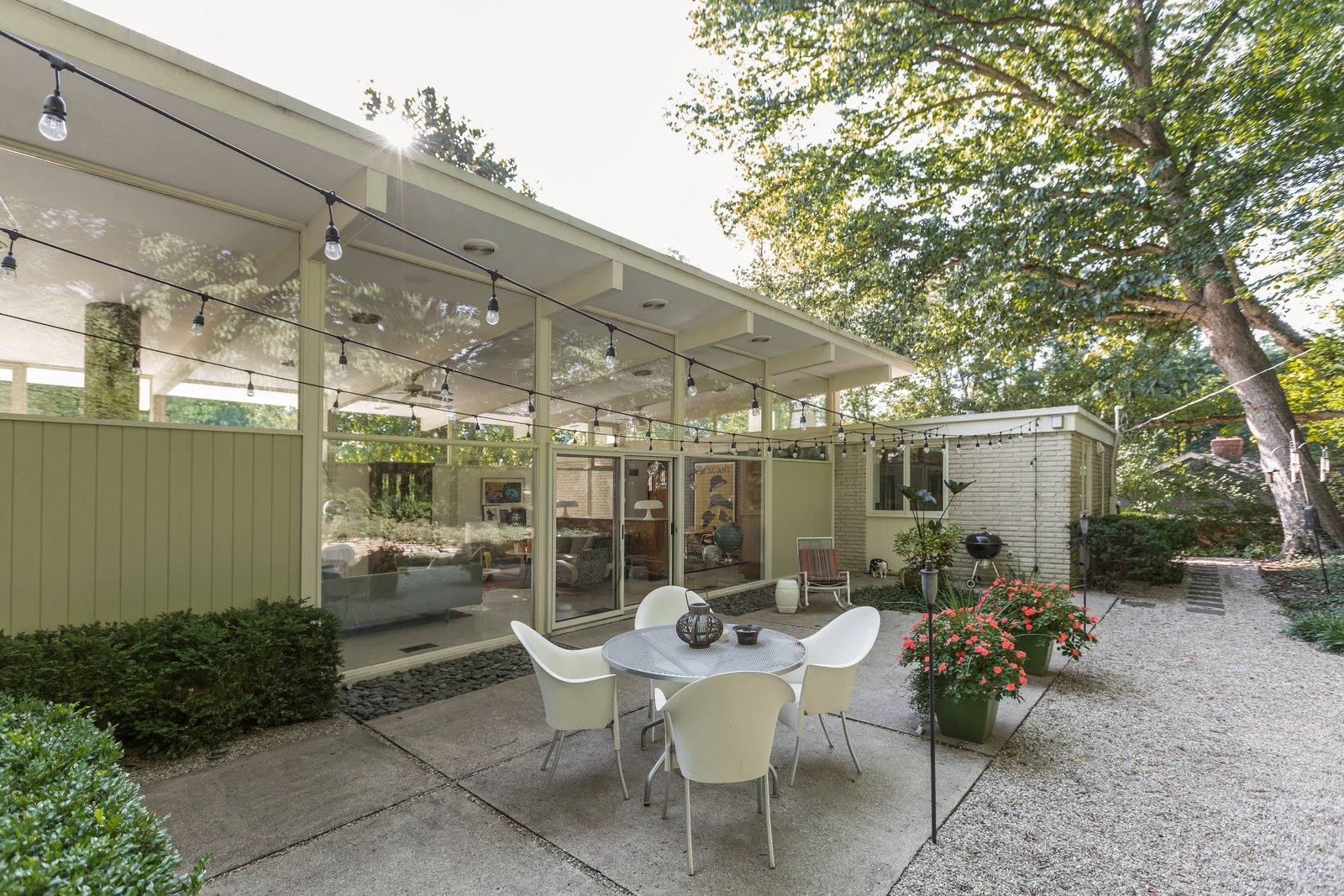 Outdoor, Pavers Patio, Porch, Deck, Concrete Patio, Porch, Deck, Back Yard, Trees, Shrubs, Grass, Hanging Lighting, and Planters Patio, Porch, Deck  Photo 9 of 10 in A Midcentury Gem by a Famed Indiana Architect Offered at $450K