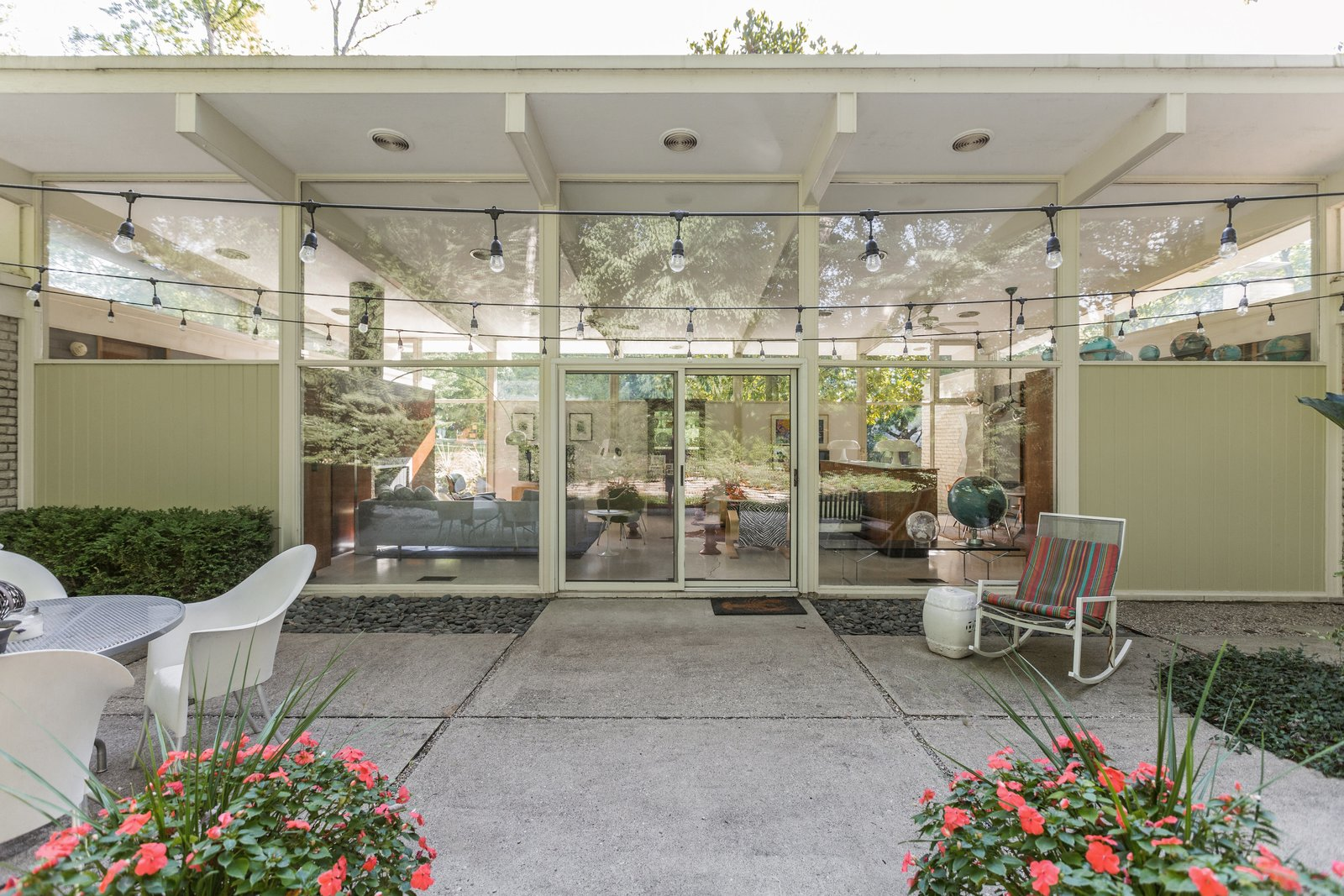 Outdoor, Pavers Patio, Porch, Deck, Raised Planters, Walkways, Concrete Patio, Porch, Deck, Planters Patio, Porch, Deck, Hanging Lighting, Gardens, Hardscapes, Flowers, and Back Yard  Photo 10 of 10 in A Midcentury Gem by a Famed Indiana Architect Offered at $450K