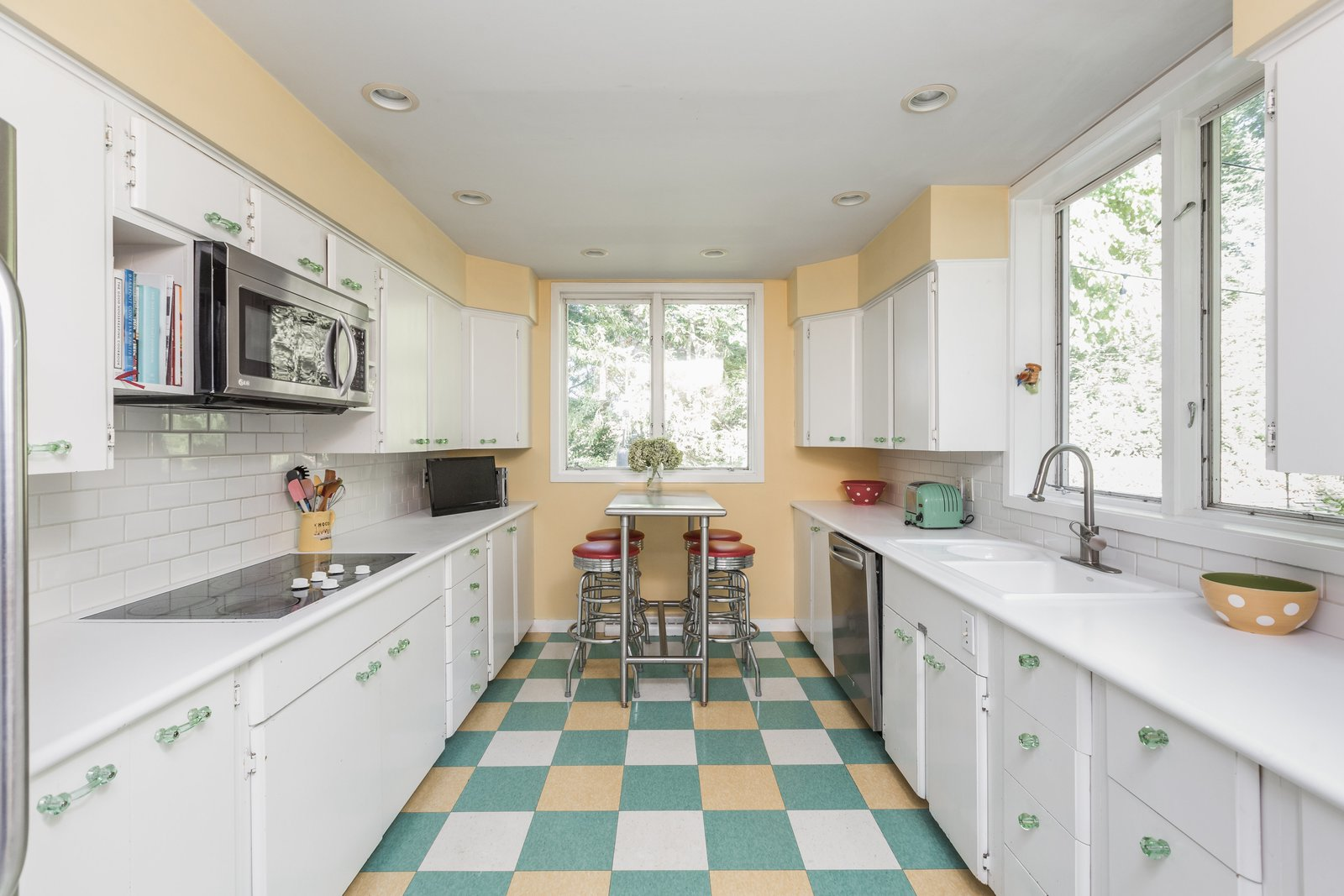 Kitchen, Refrigerator, Cooktops, Microwave, Dishwasher, White Cabinet, Drop In Sink, Recessed Lighting, and Ceramic Tile Backsplashe  Photo 6 of 10 in A Midcentury Gem by a Famed Indiana Architect Offered at $450K