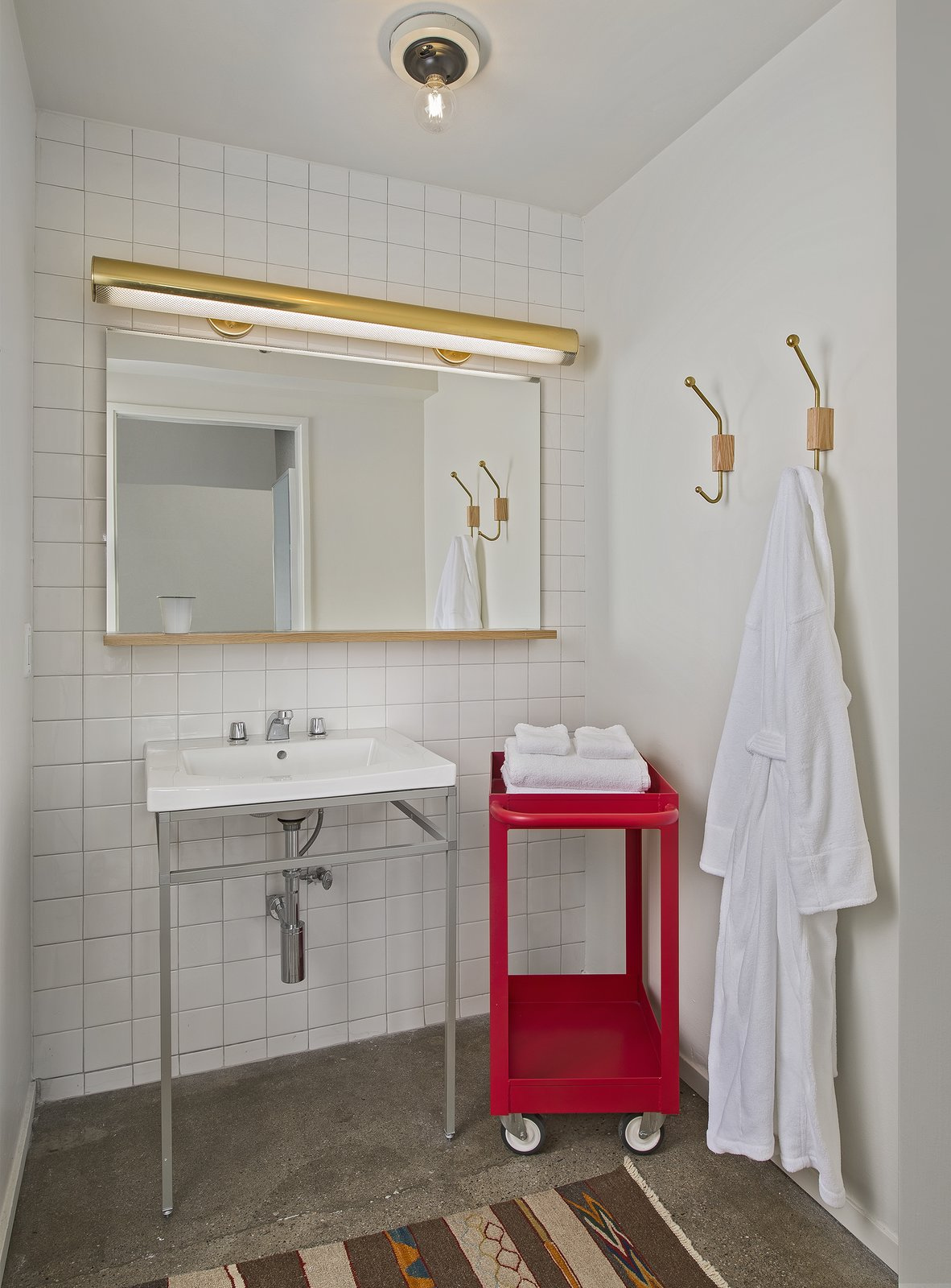 Bath Room, Concrete Floor, Wall Lighting, Pedestal Sink, Ceiling Lighting, Ceramic Tile Wall, Wall Mount Sink, and Rug Floor  Photo 13 of 15 in A Chic Detroit Hotel Showcases Local Art and Craft