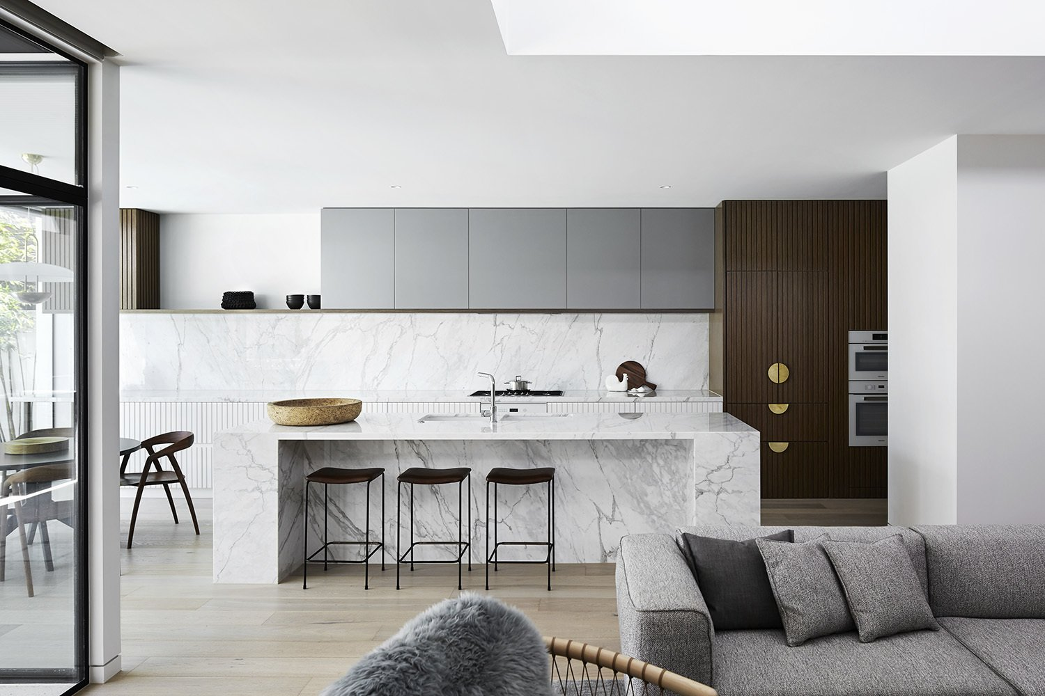 Kitchen, Wall Oven, Undermount Sink, Light Hardwood Floor, White Cabinet, Wood Cabinet, and Marble Counter  Photo 4 of 13 in A Melbourne Midcentury Gets a Palm Springs-Inspired Revival