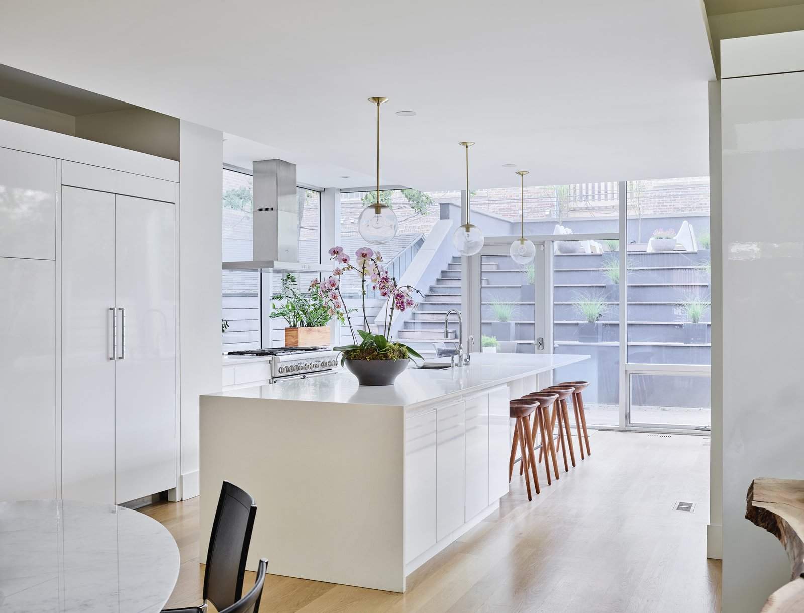 Kitchen, Refrigerator, Pendant Lighting, Light Hardwood Floor, Range, White Cabinet, Range Hood, and Undermount Sink  Photo 9 of 17 in What's the Most Overlooked Feature When Planning a Kitchen Renovation?