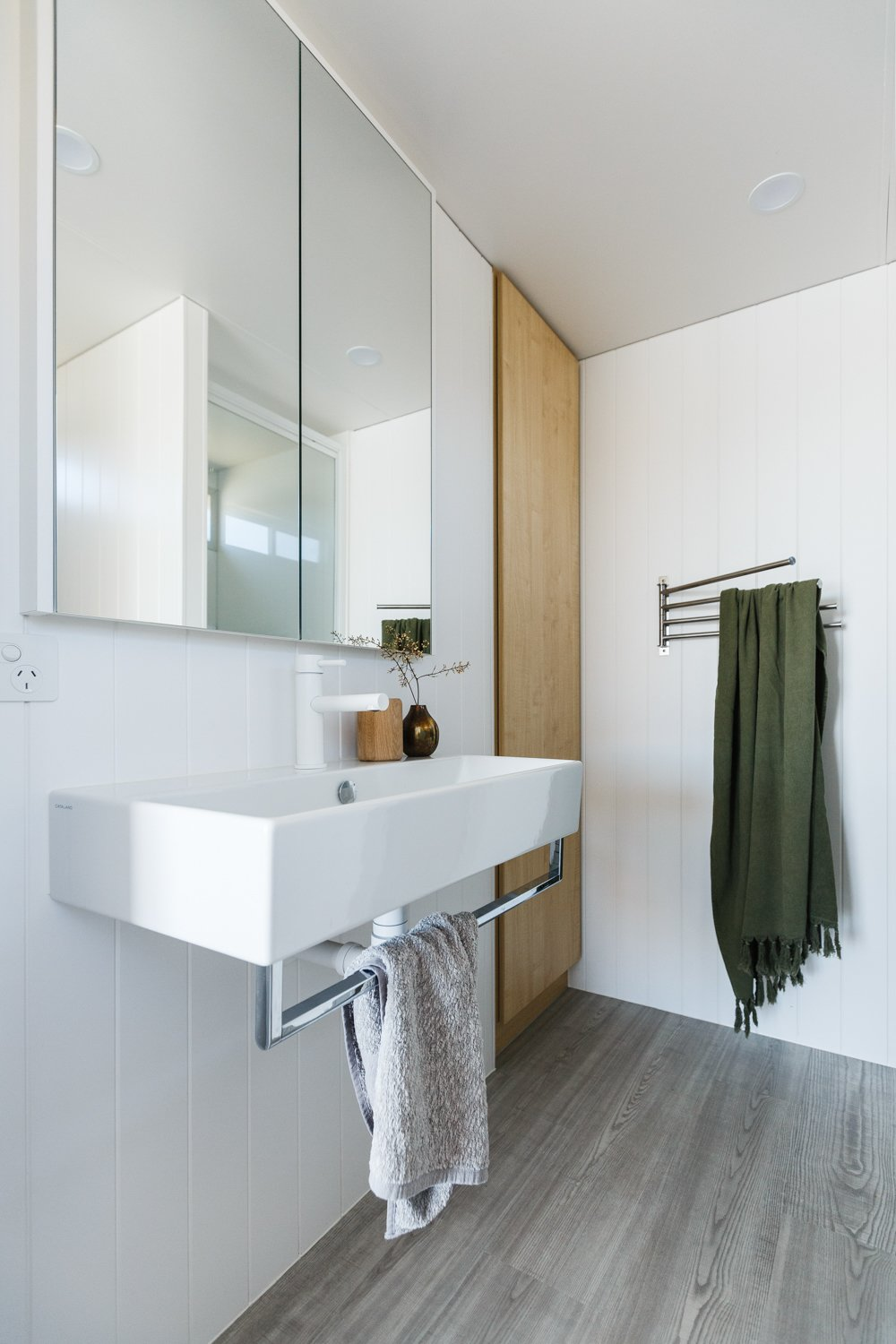 "Bath Room, Wall Mount Sink, Recessed Lighting, Laminate Floor, and Vinyl Floor In the bathroom, ""Laminex Aquapanel was selected in wet areas to meet the weight restriction and potential of cracking tiles,"" Harry said.   Photo 11 of 14 in Life in This Renovated Houseboat Would Be But a Dream"