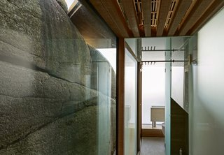 The glass wall forces focus on the texture of the surrounding cliffs.