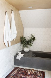 "In the bathroom, 6"" hexagon tiles from Fireclay line the wall above the tub, which is Kohler's Underscore Vibracoustic Bathtub surrounded by a custom frame finished with polished concrete."