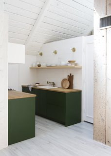 Here is a view into the kitchen, which received IKEA cabinet boxes with Semihandmade drawer and door fronts painted Chard from Behr, by Samuel. The refrigerator is a KitchenAid model tucked under the butcher block counter and covered with a panel.