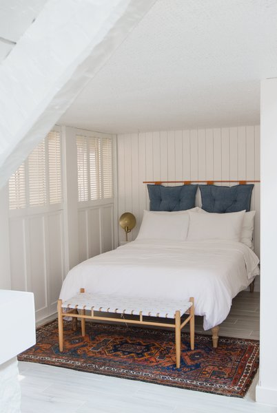 """Off the living room, Samuel uses this den as a second sleeping spot, or """"guestroom nook."""" Crumbling basket-weave texture was covered with painted wood paneling, and the headboard is a DIY."""