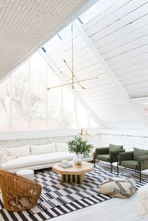 In the living room, Samuel painted the exposed wood and stonework to unify the space and let the original texture step forward. (The wood had been painted already by previous owners.) A custom ten-foot sofa sits below the window and the green canvas armchairs are from Urban Outfitters.