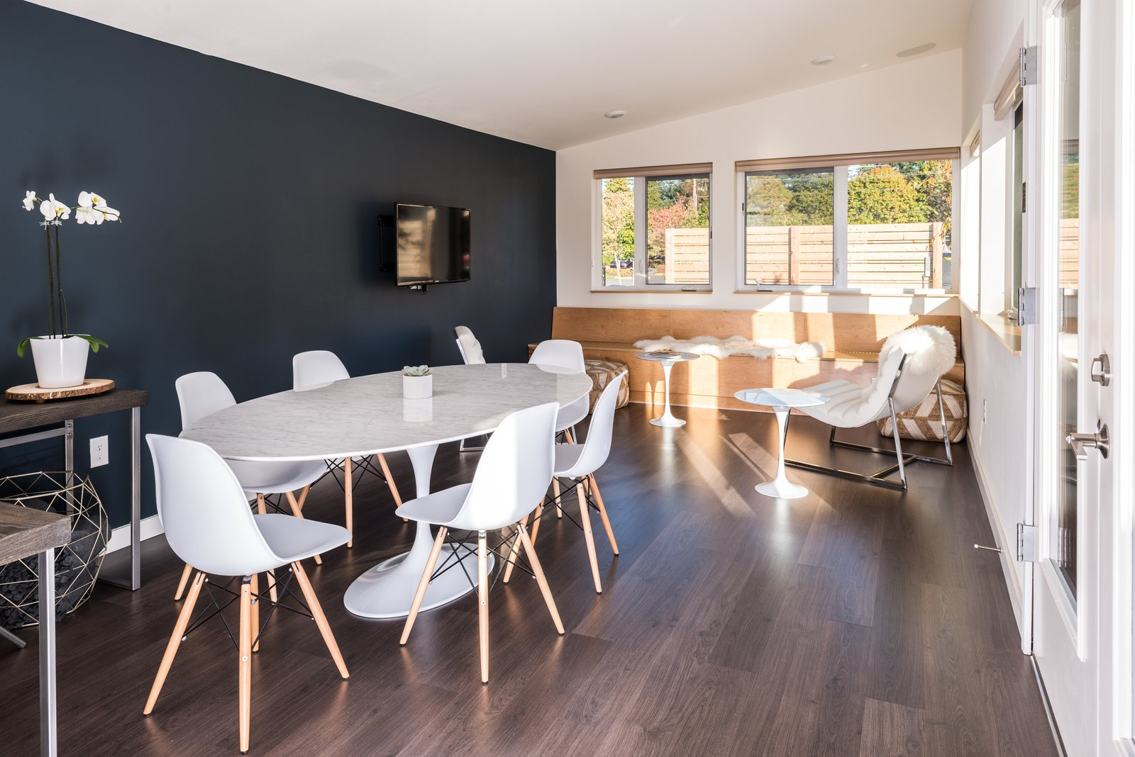 Dining Room, Ceiling Lighting, Table, Bench, Chair, Dark Hardwood Floor, and Recessed Lighting A Saarinen table and Eames chairs in the Public House.  Photo 6 of 7 in Serenity Awaits at These Prefab Cabin Rentals on Vashon Island