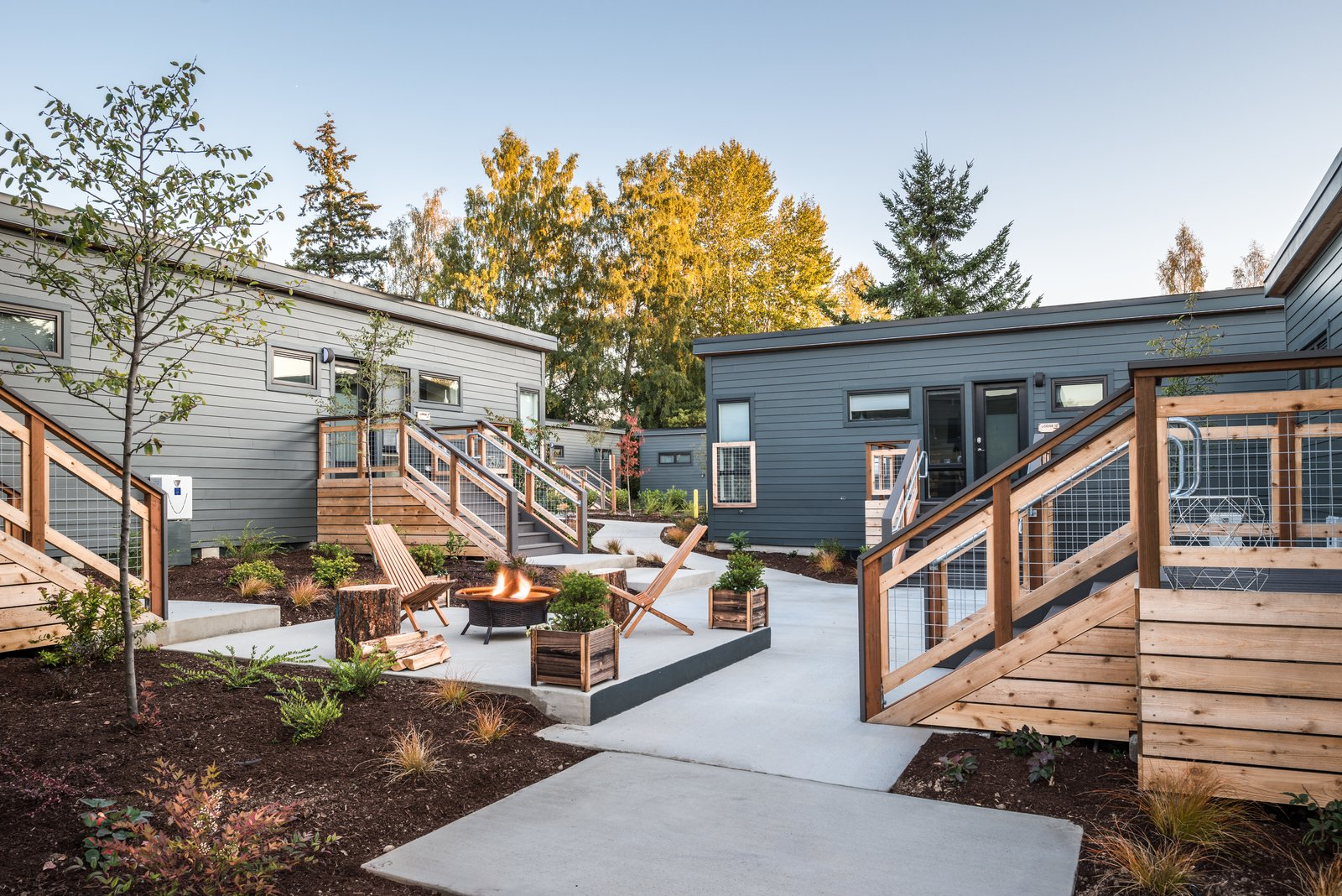 Outdoor, Planters Patio, Porch, Deck, Trees, Back Yard, Concrete Patio, Porch, Deck, Gardens, Walkways, and Raised Planters A shared courtyard with a firepit.  Photo 1 of 7 in Serenity Awaits at These Prefab Cabin Rentals on Vashon Island