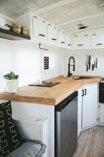 The countertops are birch-wrapped plywood. The matte black hardware and faucet punctuate white cabinets and peel-and-stick tile. A magnetic knife strip and mounted paper towel holder is another way they can save space. The dish rack is folded and stored under the sink when not in use.