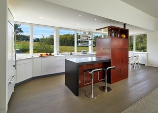 """""""Although it looks like an inoperable window, these allow for ventilation,"""" Wiedemann said of the glazing lining the kitchen and dining areas. The architects opted for Marvin Casement Venting units in custom-widths."""